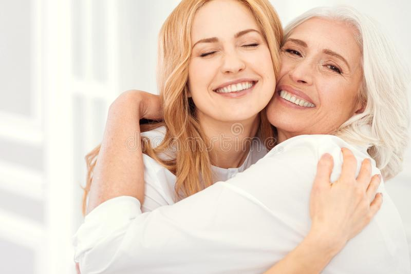 Radiant mother and daughter beaming into camera while hugging stock images