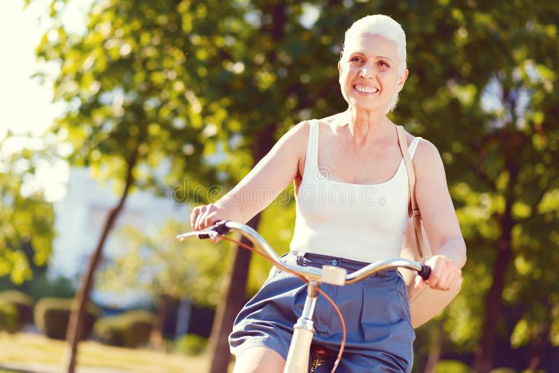Radiant retired woman grinning broadly while bicycling royalty free stock photos