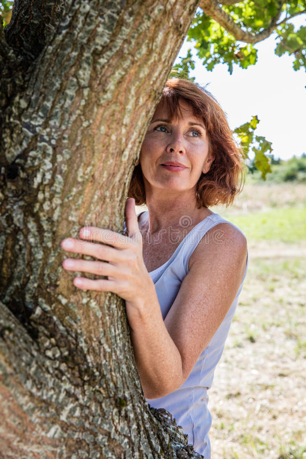 Radiant 50s woman smiling next to a tree for mature wellness. Middle aged wellness - radiant 50s woman smiling next to a tree for metaphor of mature wellness royalty free stock photo