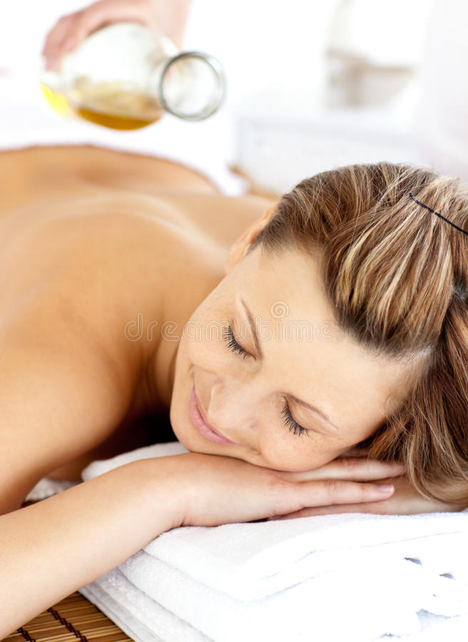 Radiant young woman having a back massage with oil stock photos