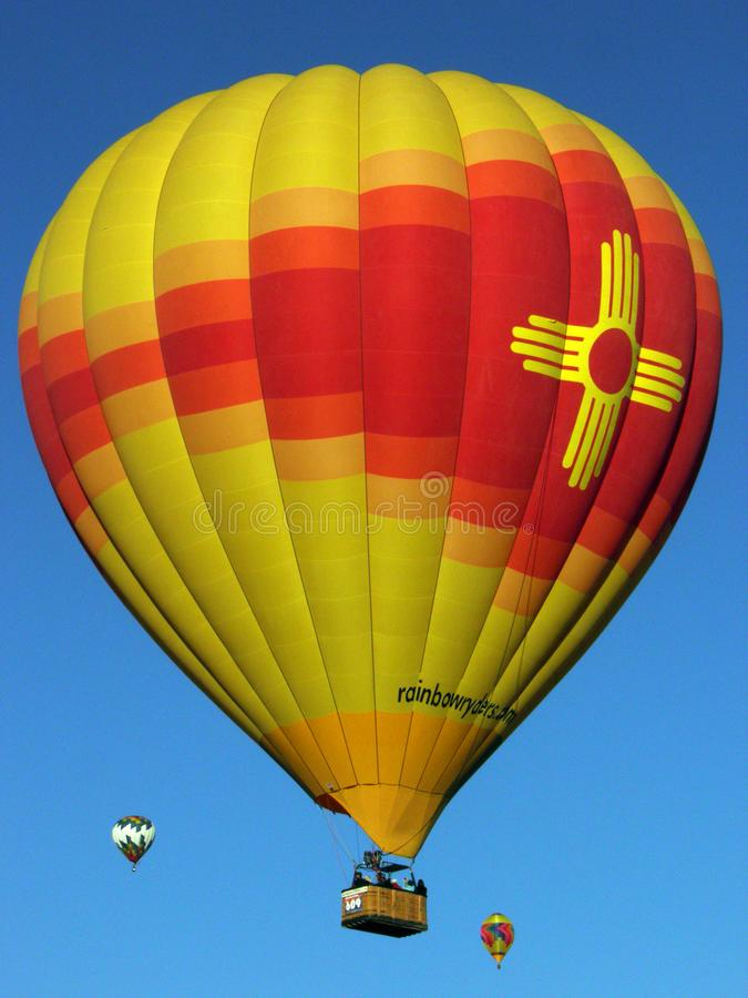 Radiant Zia balloon glowing in the skies at the Albuquerque International Balloon Fiesta. Radiant Zia over Albuquerque on a chilly morning the first weekend in royalty free stock photos