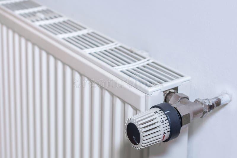 Radiateur sur un mur avec le thermostat photographie stock