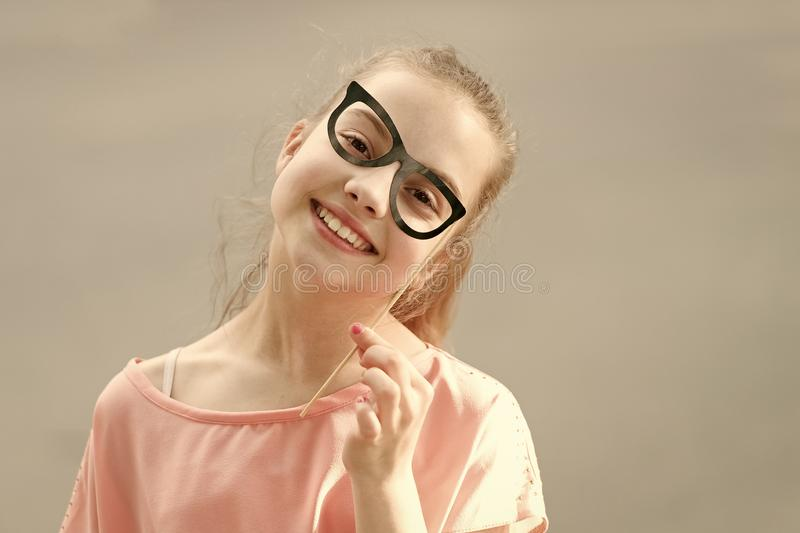 She is radiating happiness. Small smiling girl with funny look through prop glasses. Happy little child with adorable royalty free stock images