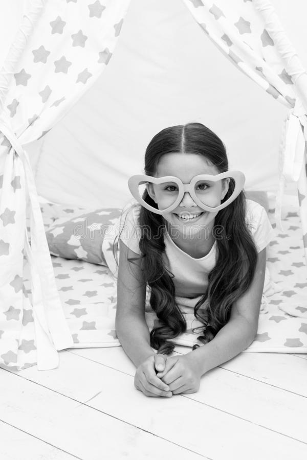 She is radiating love. Girl cute child in heart shaped eyeglasses lay relaxing in teepee in her bedroom. Cute space for. Childrens leisure. Modern childrens royalty free stock images
