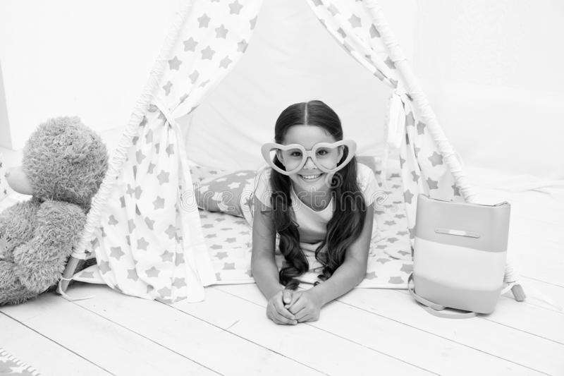 She is radiating love. Girl cute child in heart shaped eyeglasses lay relaxing in teepee in her bedroom. Cute space for. Childrens leisure. Modern childrens stock photography