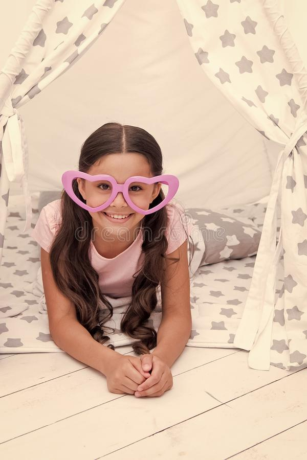 She is radiating love. Girl cute child in heart shaped eyeglasses lay relaxing in teepee in her bedroom. Cute space for. Childrens leisure. Modern childrens stock image