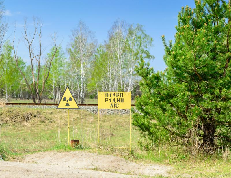 Radiation hazard sign in the red forest near the town of Pripyat. Chernobyl Exclusion Zone. stock image