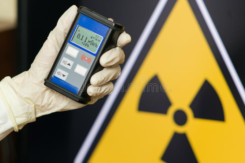 Radiation supervisor in glove with geiger counter checks the level of radiation. In the radioactive zone royalty free stock photography
