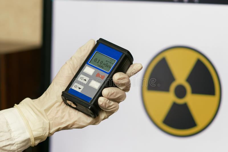 Radiation supervisor in glove with geiger counter checks the level of radiation. In the radioactive zone stock photo