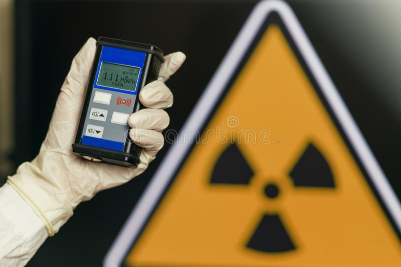 Radiation supervisor in glove with geiger counter checks the level of radiation. In the radioactive zone royalty free stock images