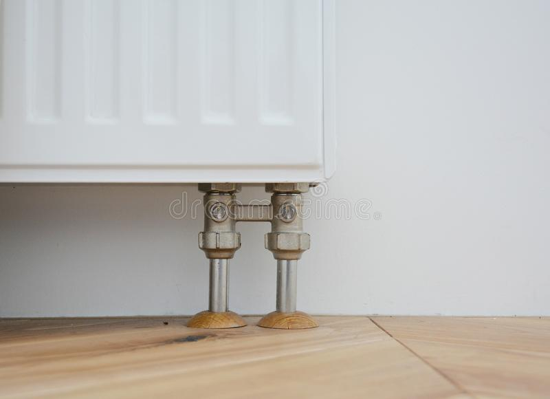 Radiator pipe covers sleeves. Install radiator for heating system with hiding pipes in the wooden floor. Radiator pipe sleeves stock photo