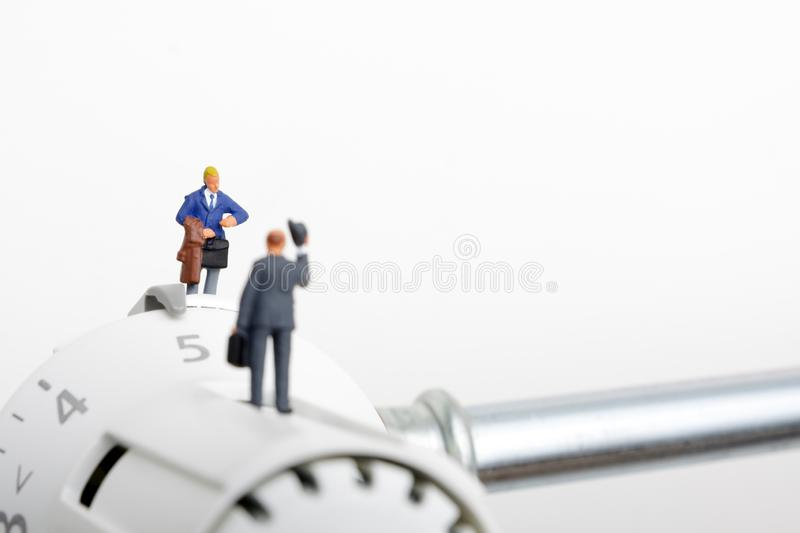 Radiator and small figurines. Two businessmen and heating battery. Two customers or consumers and heating battery stock photo