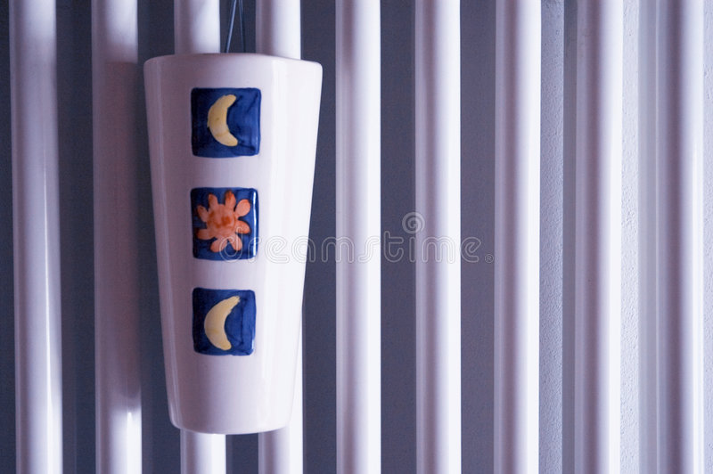 Radiator surface with humidifier. Closeup view of radiator surface with humidifier in violet light stock photo