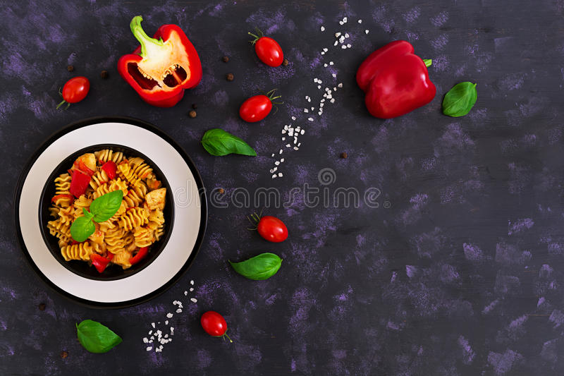 Radiatori pasta with chicken and peppers on dark background. Top view stock image