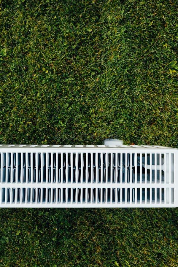 Radiatornetwerk op groen gazon, ecologisch het verwarmen concept stock afbeeldingen