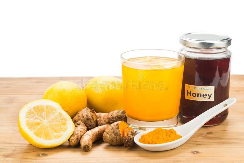 Radici di curcuma con le bevande del miele e del limone, bev curativo potente immagini stock libere da diritti