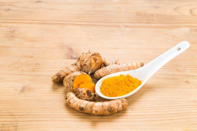 Radici di curcuma e polvere, alimento sano con le proprietà curative immagine stock libera da diritti