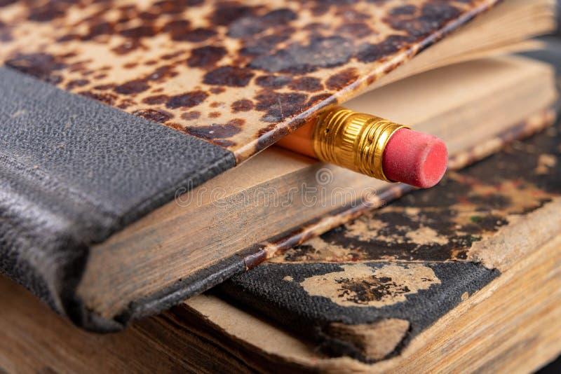 Radiergummi gesprungen auf einen Bleistift und ein altes Buch Schreiben von Zus?tzen und von B?chern auf eine alte Tabelle lizenzfreies stockbild