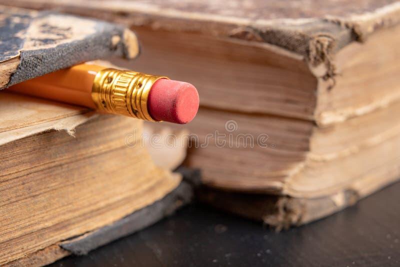 Radiergummi gesprungen auf einen Bleistift und ein altes Buch Schreiben von Zus?tzen und von B?chern auf eine alte Tabelle lizenzfreie stockbilder