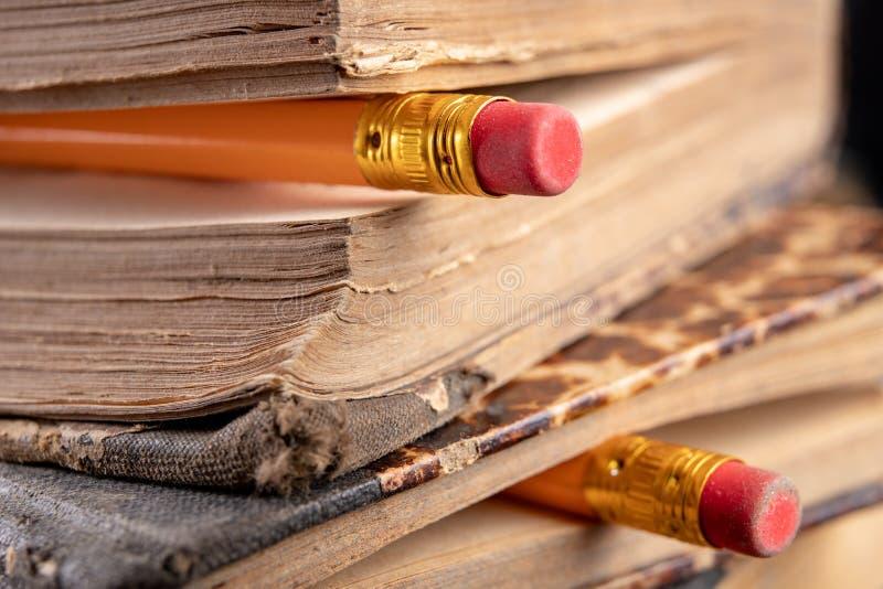 Radiergummi gesprungen auf einen Bleistift und ein altes Buch Schreiben von Zus?tzen und von B?chern auf eine alte Tabelle stockfotografie