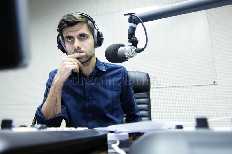 Radio anchorman hosts the serious evening show. Radio anchorman hosts the program on air stock photography