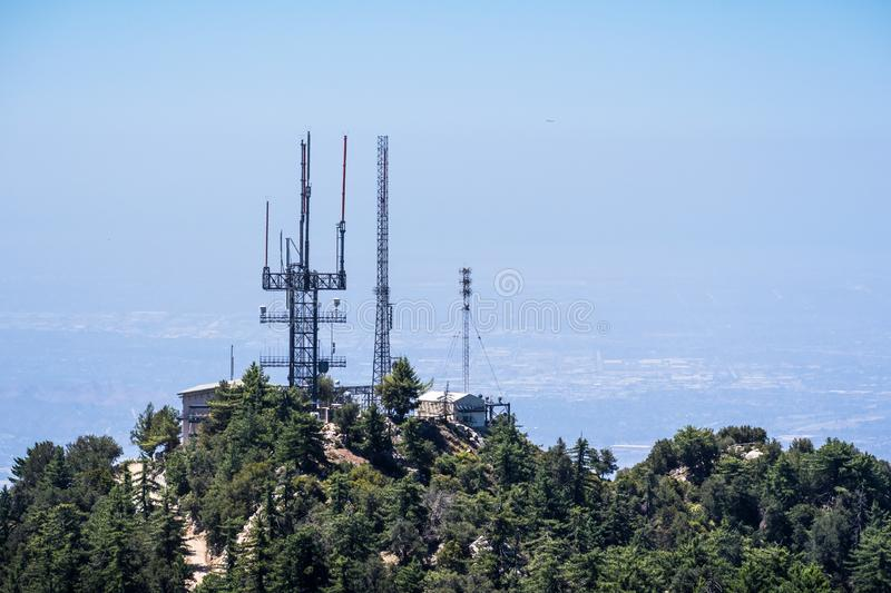 Radio antennas on the mountains of Angeles National Forest, haze covering the valley in the background; Los Angeles county, royalty free stock photography