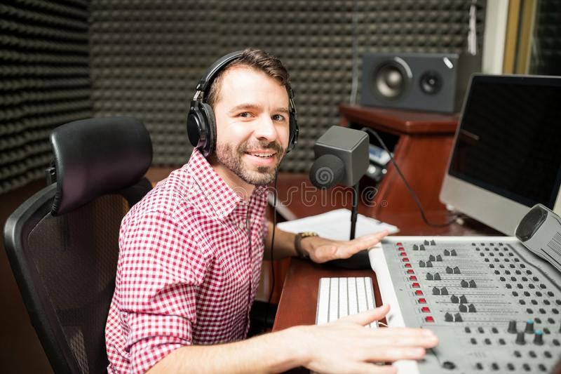Radio broadcaster at studio. Portrait of handsome male radio presenter at sound studio with sound mixed console and microphone royalty free stock photo