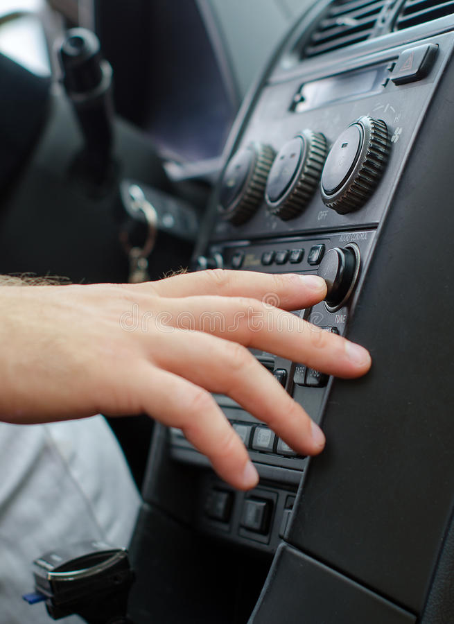 Radio in the car. Man's hand tuning radio in the car royalty free stock photography