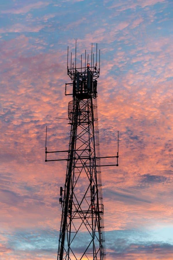 Radio et tour de communications d'?mission t?l?vis?e dans le dos de Ridge de foudre allum? par un coucher du soleil rose image libre de droits