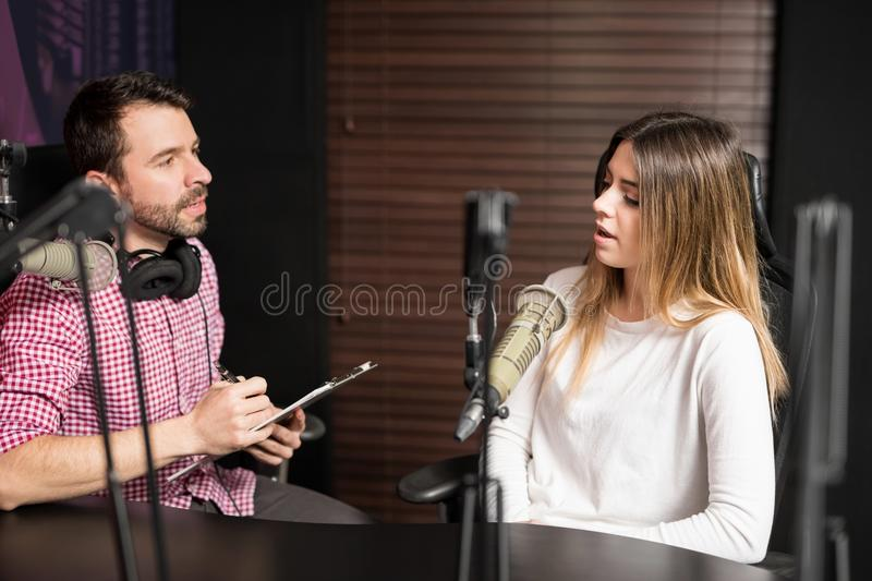Radio podcast interview. Hispanic men and women podcasters talking with each other for radio podcast royalty free stock image