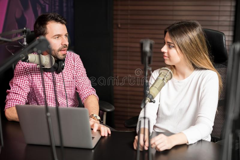 Radio presenter interviewing a guest for podcast. Portrait of male radio presenter interviewing a women guest in a radio studio for a podcast stock photography