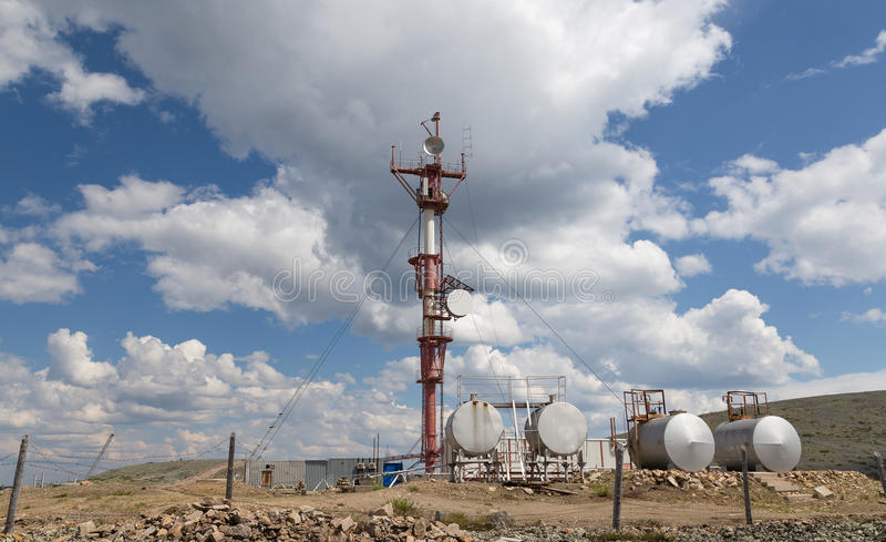 Radio relay station. Broadcasting complex against a blue sky with clouds royalty free stock photography