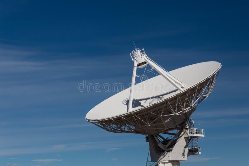 Radio satelliet de schotelantenne van Very Large Array die tegen een diepe blauwe hemel wordt geïsoleerd stock foto's