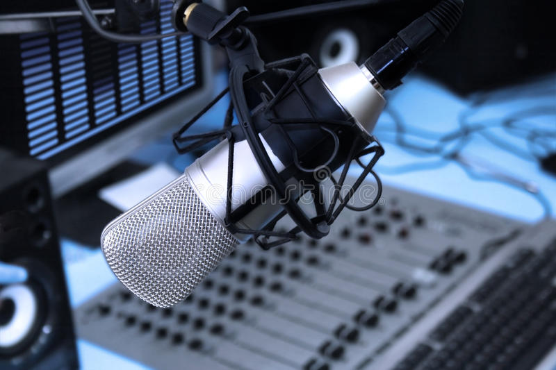 In radio studio. A mic in front of the control panel in broadcasting studio