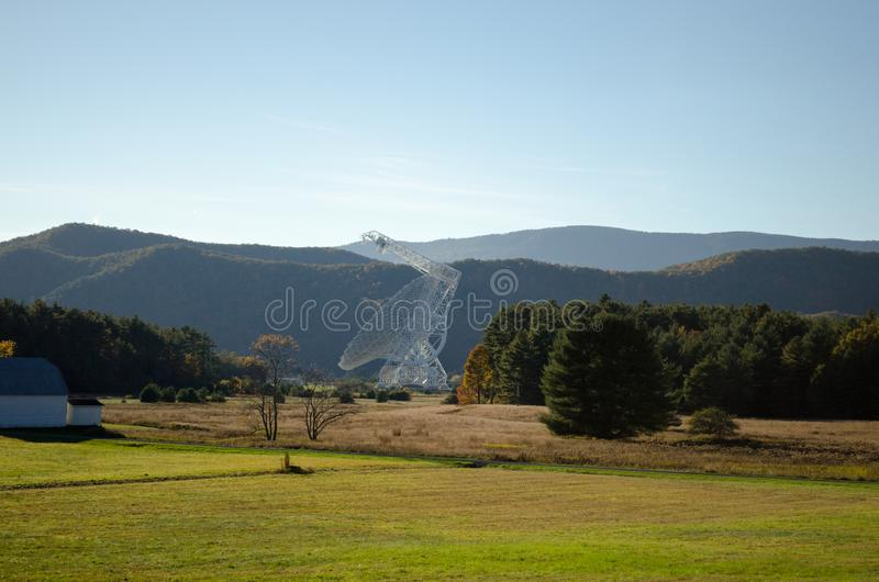 Radio Telescope In West Virginia with Mountains In the Background. A radio telescope in West Virginia. It`s white and made of metal. This is from Green Bank West stock photos
