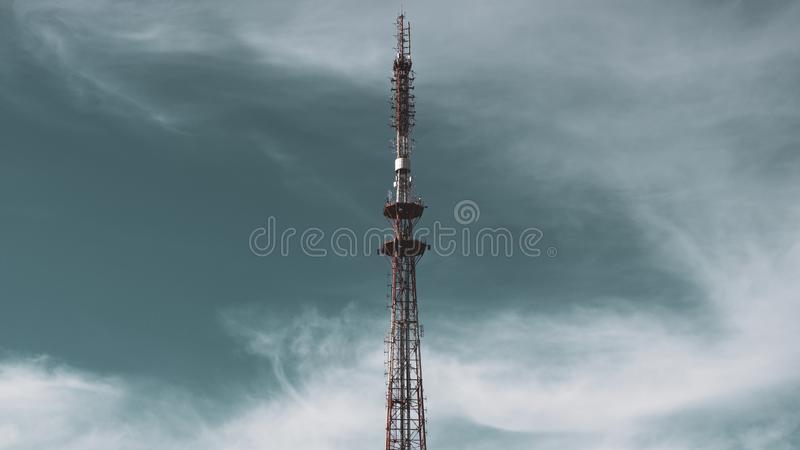 Radio tower antenna on a background of blue sky with white clouds. Telecommunication transmitter global telephone equipment. Vertical photo stock photography