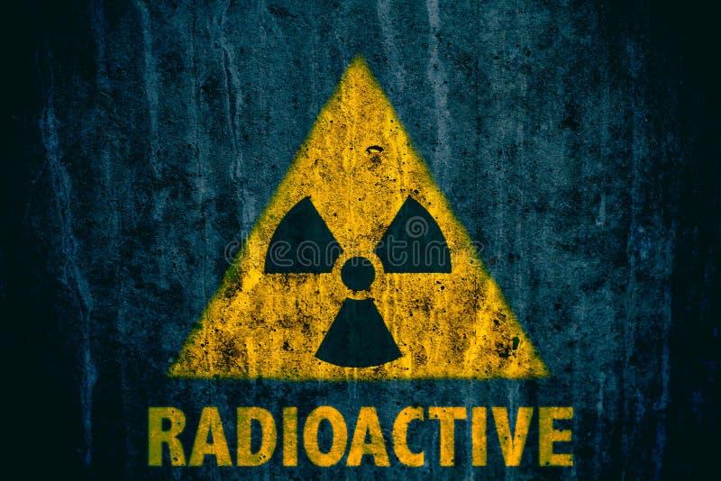 Radioactief ioniserende stralinggevaarsymbool met woord radioactieve die onderstaand op een massieve concrete muur wordt geschild royalty-vrije stock foto's
