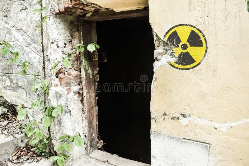Radioactief waarschuwingsbord op de grunge vuile muur in de verlaten bouw van de uitsluitingsstreek De atmosfeer van Tchernobyl P stock afbeelding