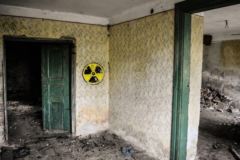 Radioactief waarschuwingsbord op de grunge vuile muur in de verlaten bouw van de uitsluitingsstreek De atmosfeer van Tchernobyl P stock afbeeldingen