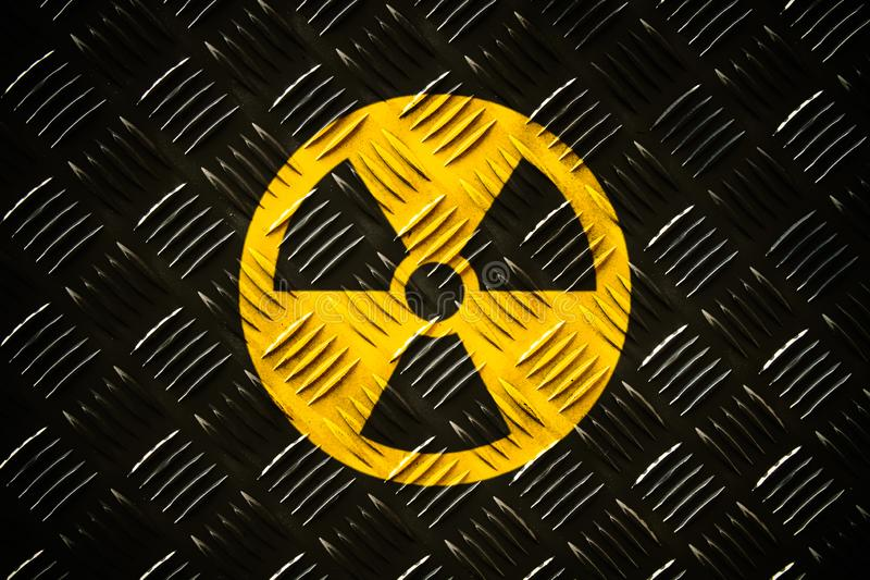 Radioactive ionizing radiation round yellow and black danger symbol painted on a massive steel checker metal diamond plate stock images