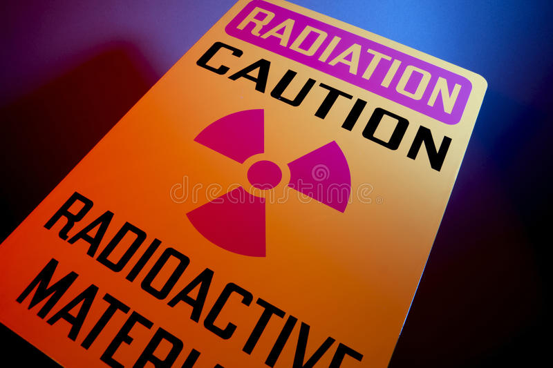 Radioactive materials sign. Orange radiation sign shot at dramatic angle with glowing background royalty free stock photo