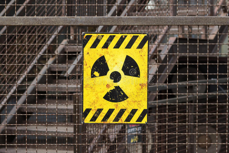 Radioactive warning sign on rusty fence. Yellow radioactive warning sign on rusty fence royalty free stock photography