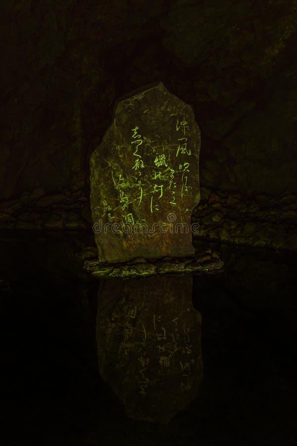 Radioaktiver Felsen in einer Höhle mit grünen Tönen und japanischen kanjis, die enoshima Höhlenschongebiet liest stockfotografie