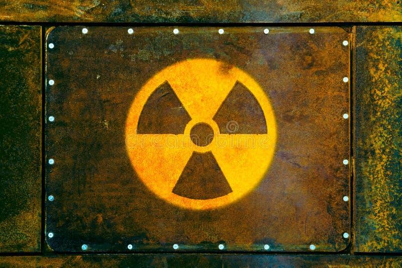 Radioaktivt symbol: det runda gula radioaktiva symbolet för varning för fara för joniseringsutstrålning målade på en massiv rosti arkivbilder