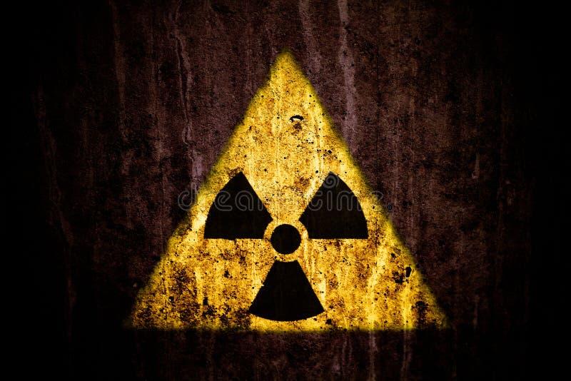 Radioaktivt symbol för guling för fara för joniseringsutstrålning över en massiv sprucken betongvägg med och en mörk lantlig grun royaltyfri foto