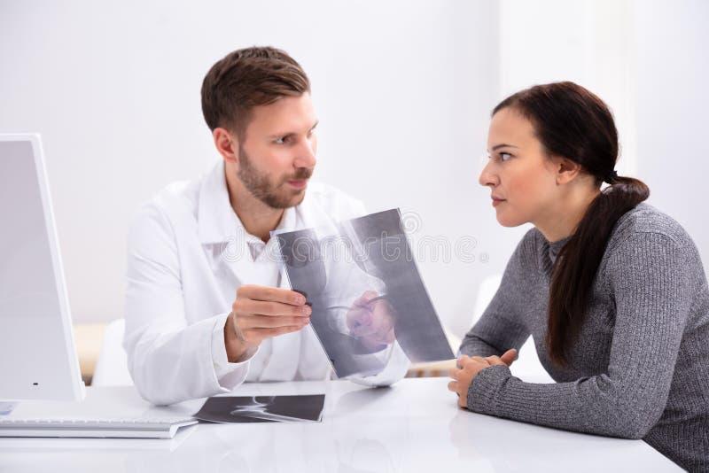 Radiograf?a del doctor Showing Knee al paciente foto de archivo libre de regalías