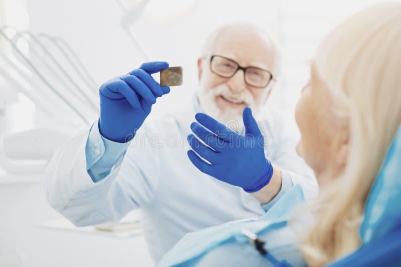 Radiografia maschio allegra del dente di rappresentazione del dentista fotografia stock