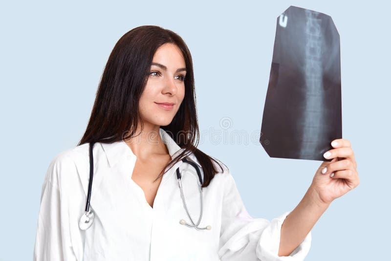 Radiografie en geneeskundeconcept De tevreden jonge professionele vrouwelijke arts onderzoekt patiëntenbackbone op Röntgenstraal, royalty-vrije stock foto's