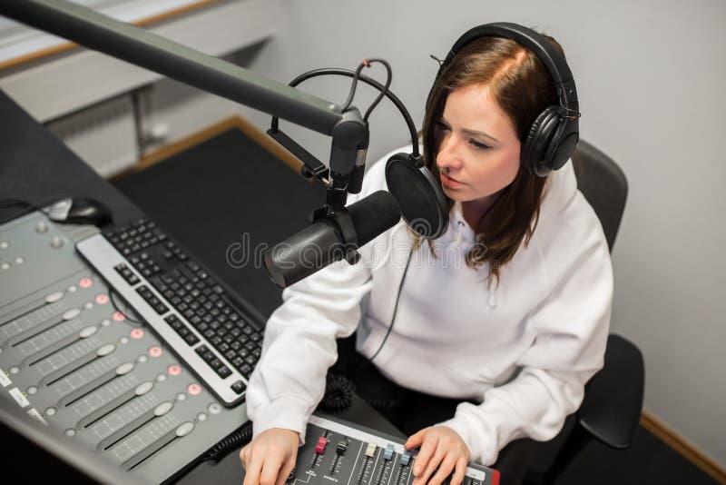 Radiojockey Using Music Mixer beim In Verbindung stehen auf Mikrofon stockfotografie