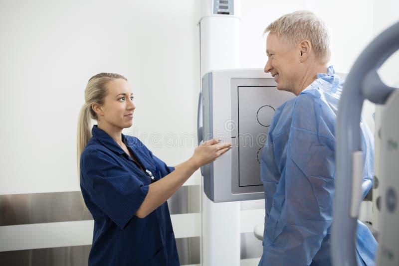 Radiolog Gestykuluje W kierunku Xray maszyny Podczas gdy Patrzejący Pati zdjęcie royalty free
